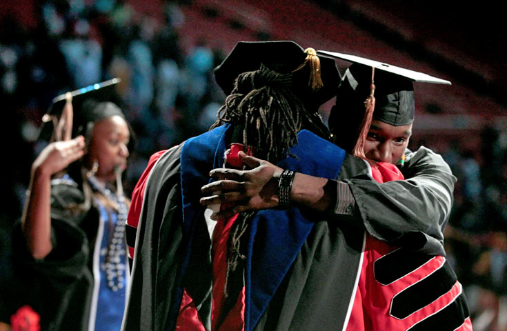 African American male student crossing stage during graduation ceremony