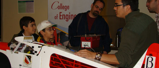 Engineering students explain an exhibit to some young students